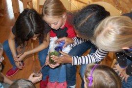 Kinder beim Versuch, mit blauer Tinte gefärbstes Wasser in einem selbst hergetellten Bodenfilter zu reinigen.