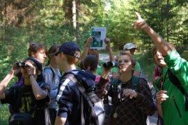 SchülerInnen beobachten mit Swarovski-Ferngläsern die Natur im Wald.
