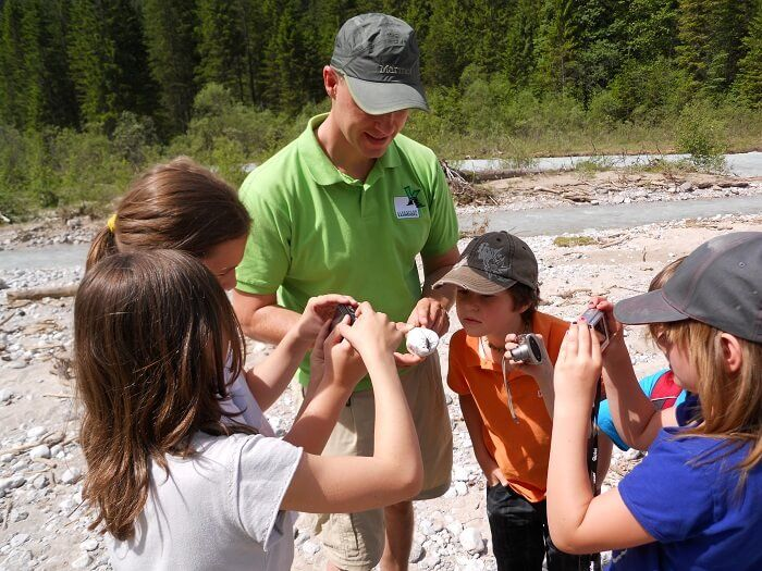 Kinder mit Naturführer am Fluss