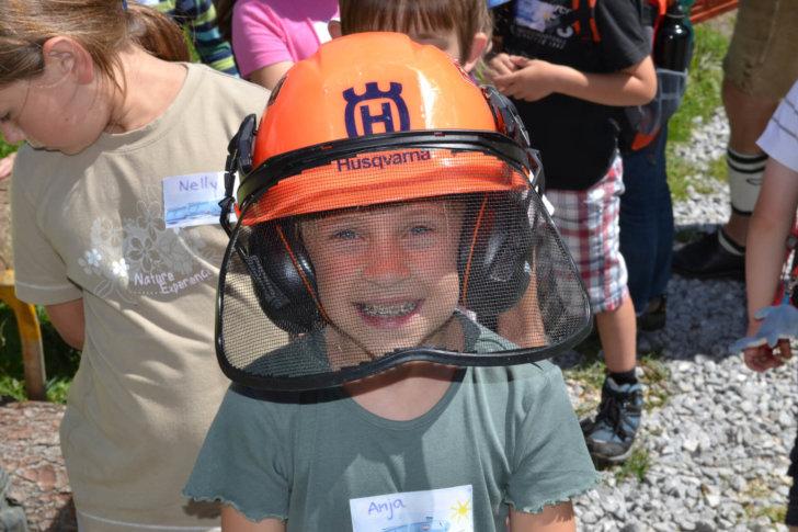 Lächelndes Kind mit Schnittschutzhelm von Husquarna.
