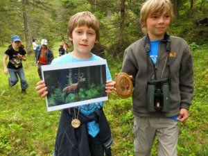 Zwei Junior Ranger im Naturpark Karwendel mit Swarovski Fernglas, Hufabdruck und Foto eines Rothirsches.
