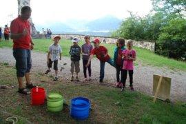6 Kinder werfen bei der Karwendelolympiade Zapfen in einen roten, grünen oder blauen Falteimer. Es ist eine Zielwurfübung.