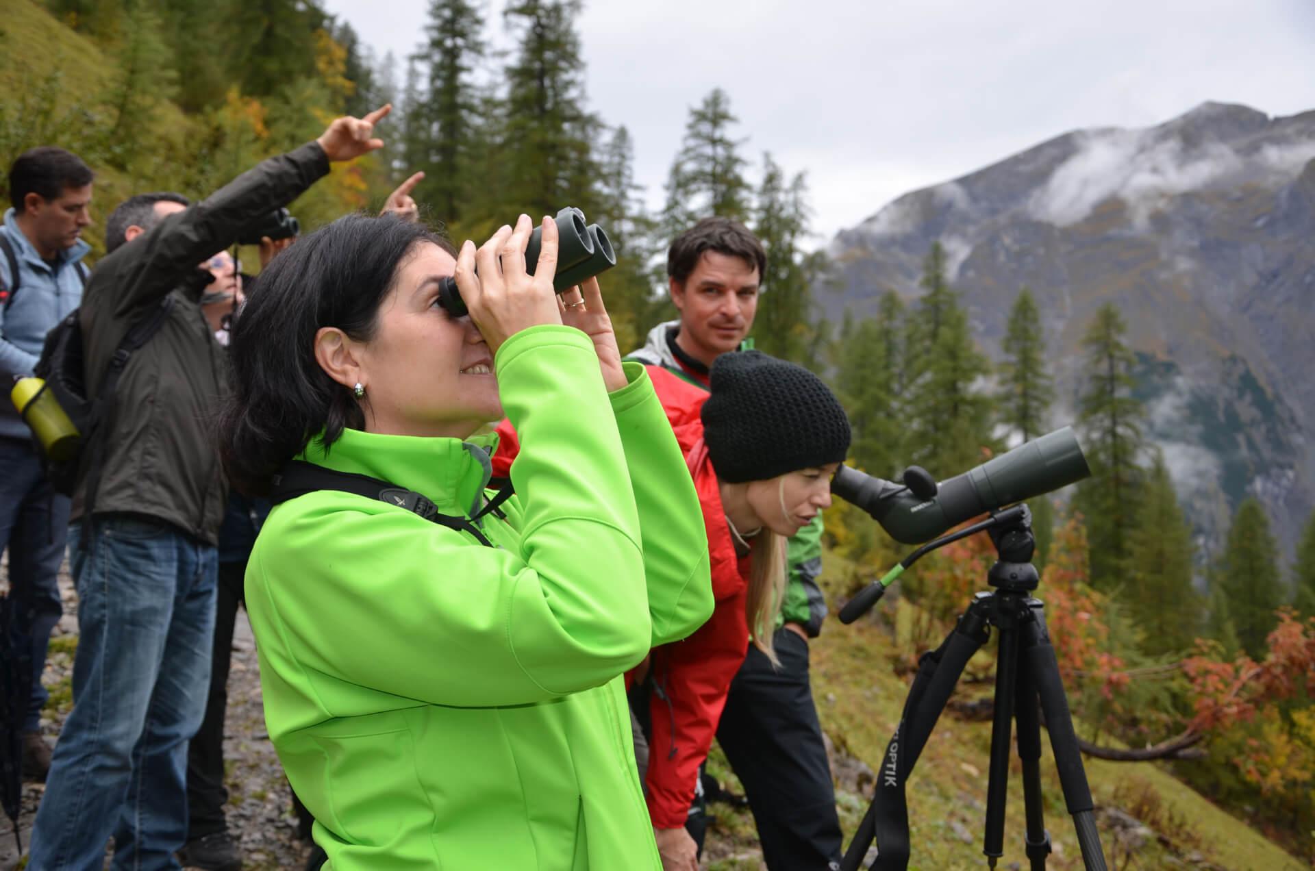 Naturführung mit Hermann Sonntag, wobei die TeilnehmerInnen mit Fernoptik von Swarovski Optik Ausschau nach Tieren halten.