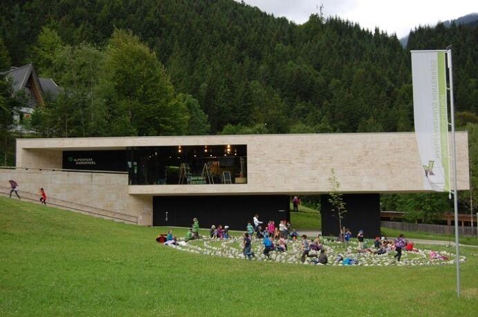Naturparkhaus mit Labyrinth und spielenden Kindern im Vordergrund