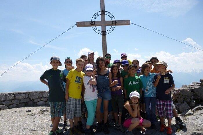 Schülergruppe vor dem Gipfelkreuz auf dem Hafelekarspitz bei blauem Himmel.