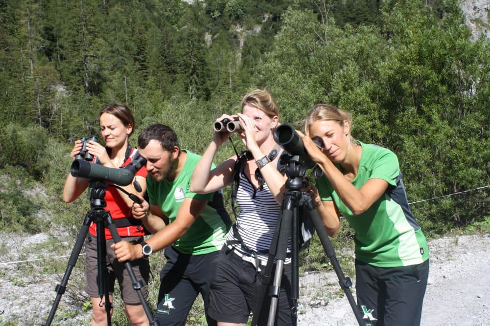 Die Naturpark-Ranger Sina Hölscher und Sebastian Pilloni mit 2 Teilnehmerinnen beim Beobachten mit Ferngläsern und Spektiven von Swarovski Optik.