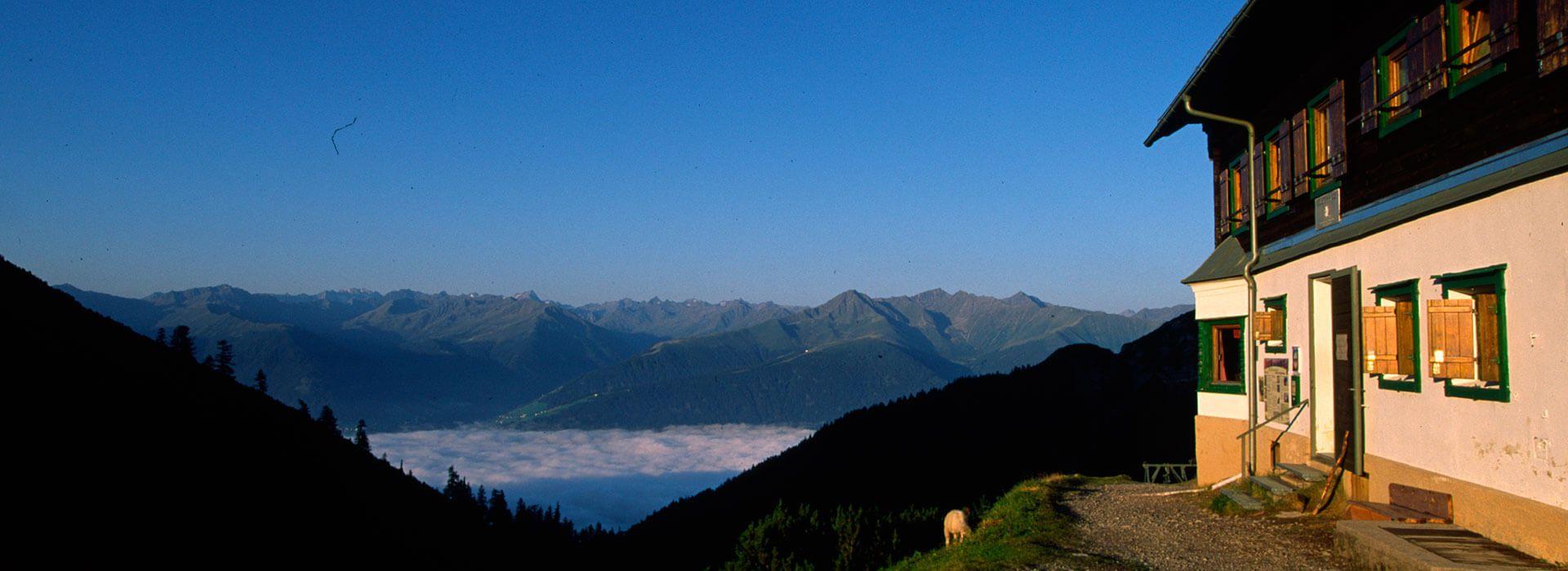 Blick am Solsteinhaus vorbei Richtung Süden mit Nebel über dem Inntal.