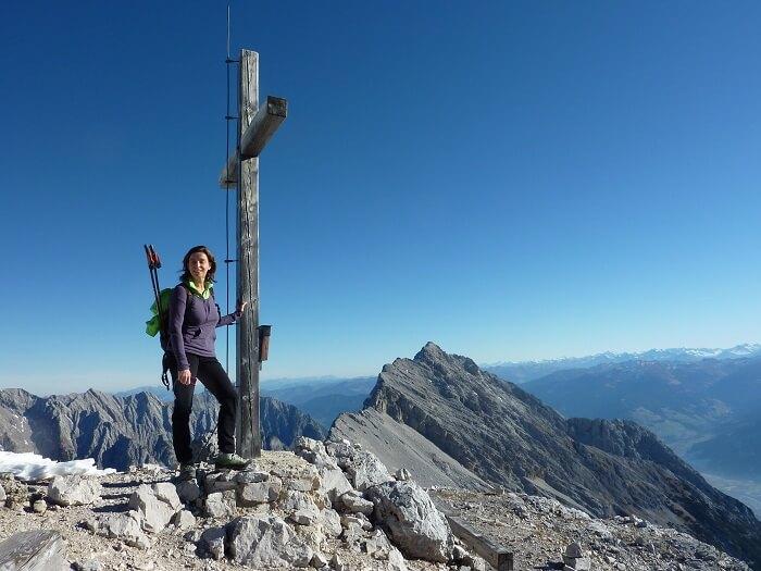 Wanderin am Gipfelkreuz der Speckkarspitze